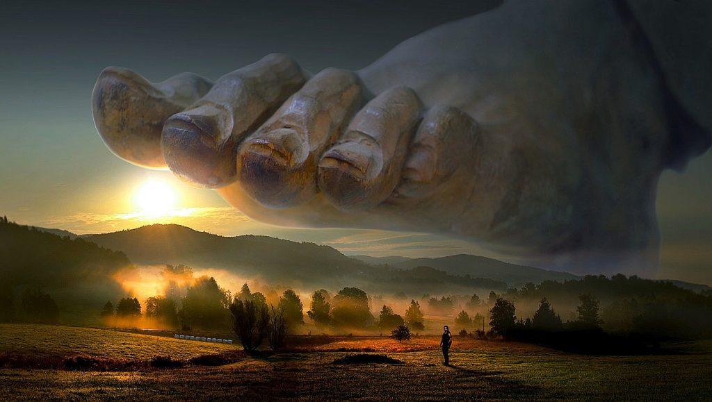 Ein riesiger Fuß über einer etwas düsteren Sonnenuntergangslandschaft, in der ein winzig kleiner Mensch zu sehen ist.