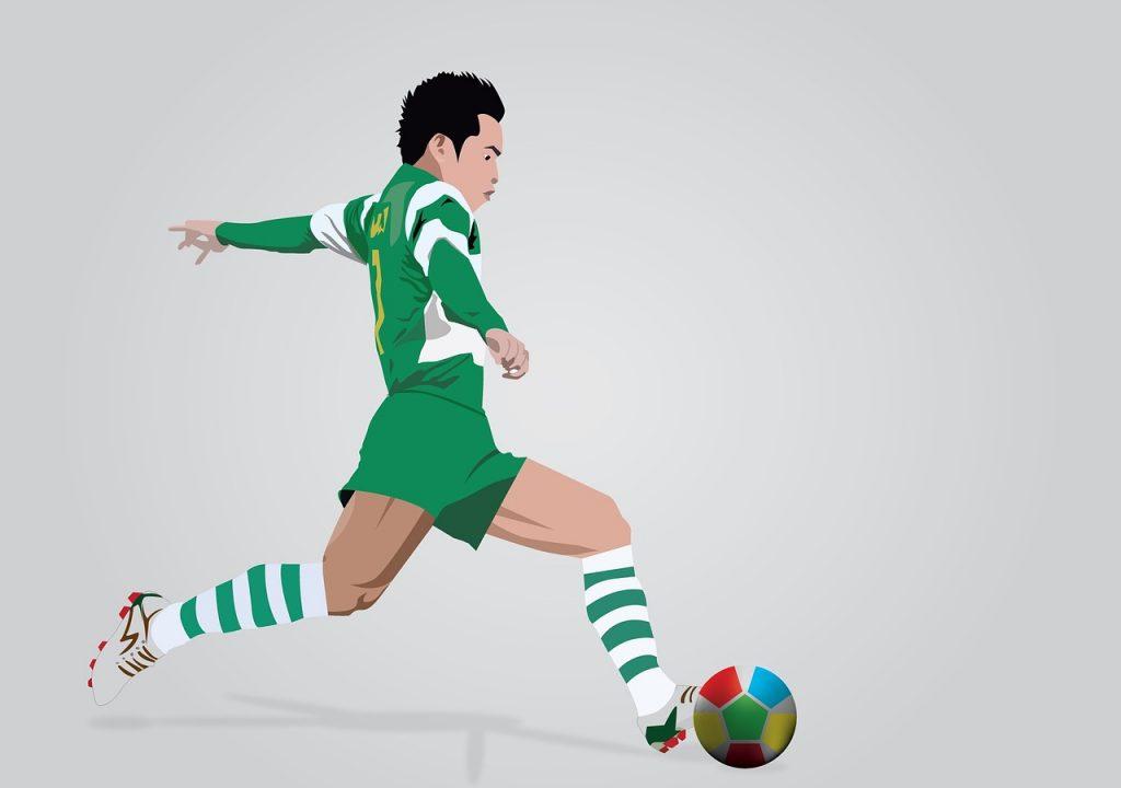 Fußballer in grünem Trikot läuft hinter einem Fußball her