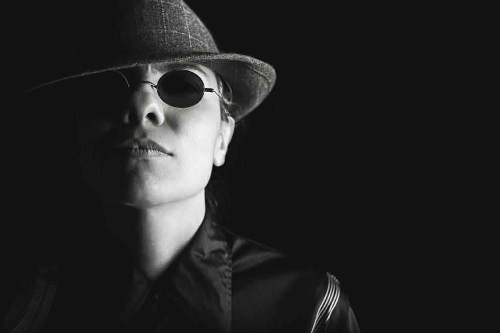 Ein junger Mann mit Sonnenbrille und Al-Capone-Hut im Dunkeln