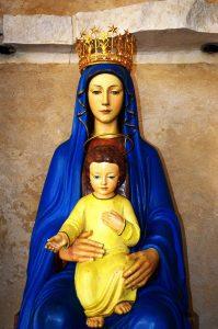 Madonna-Statue: Maria mit goldener Krone und blauem Gewand hält vor sich auf dem Schoß das schon etwas ältere Jesuskind, in Gelb gekleidet.
