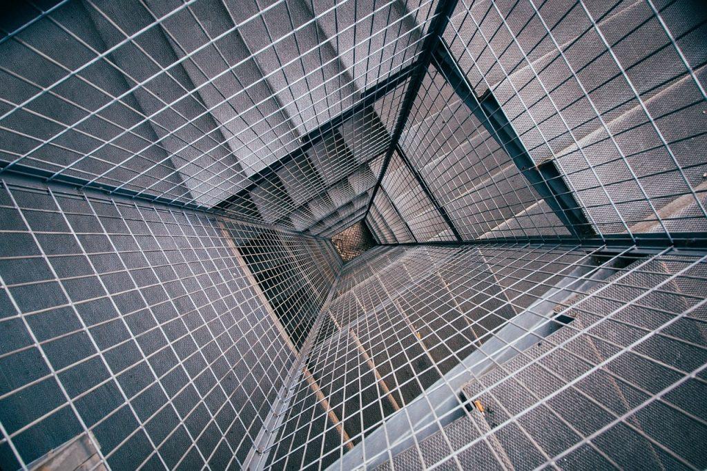 Ein Blick von oben in den Abgrund eines von Gittern umfriedeten Treppenhauses