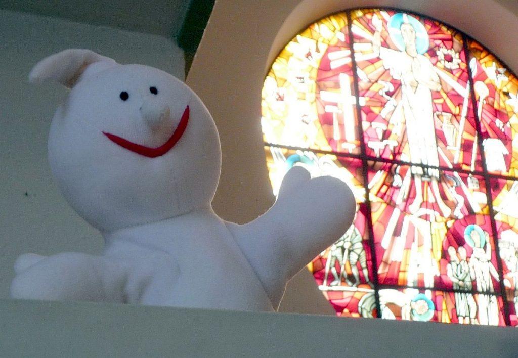 Die Handpuppe Gabi, die wie ein weißes Gespenst aussieht, vor dem Paulus-Altarfenster