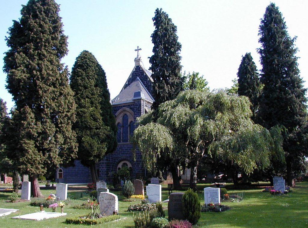 Gräber auf dem Neuen Friedhof Gießen im Schatten der Friedhofskapelle