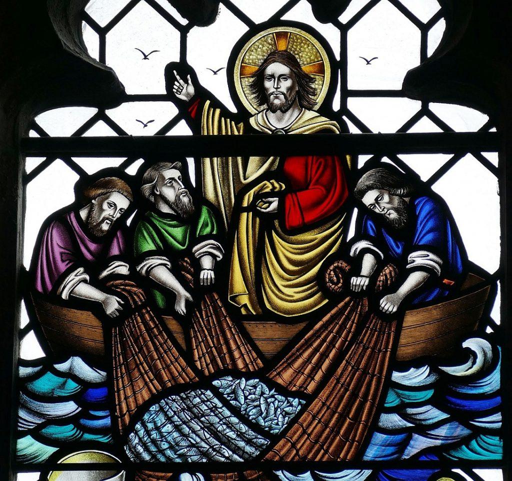 Kirchenfenster mit Jesu reichlichem Fischfang: Er sitzt im Boot mit drei Jüngern, die ihr gefülltes Netz präsentieren