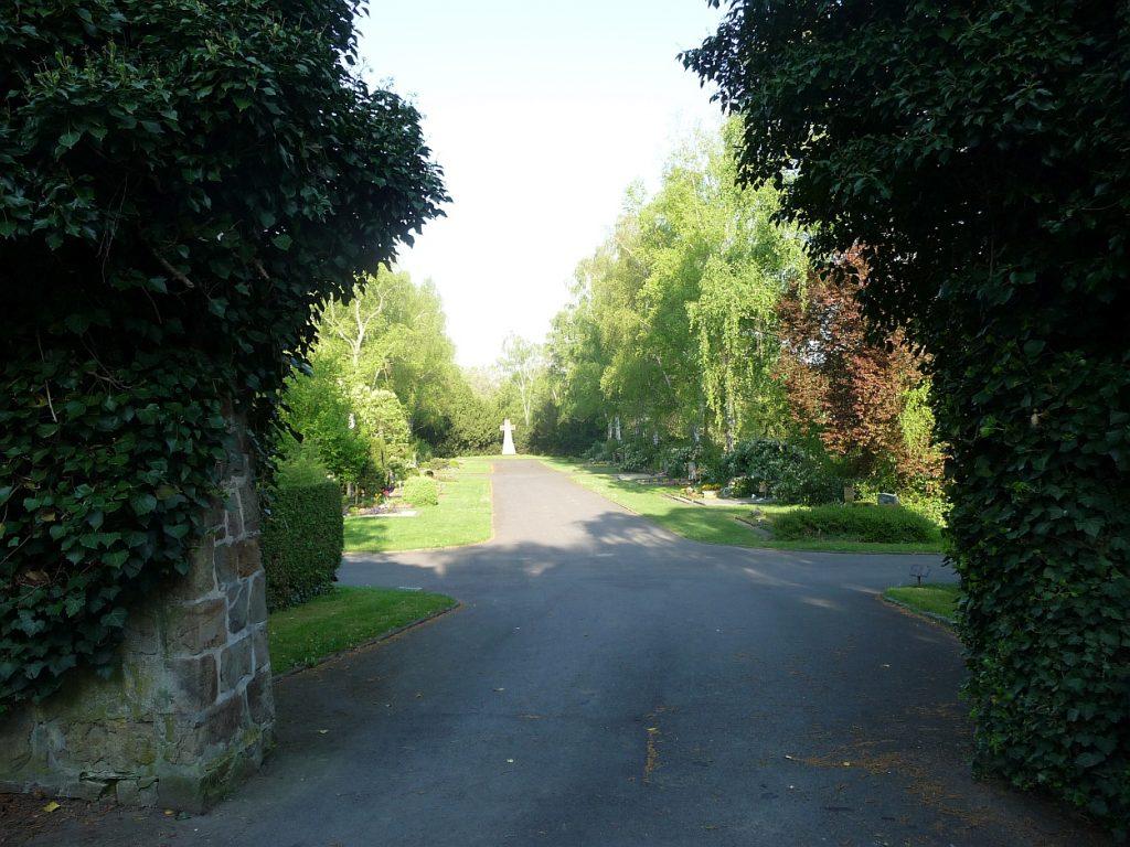Blick durch eine Maueröffnung zum Steinkreuz auf dem Neuen Friedhof Gießen