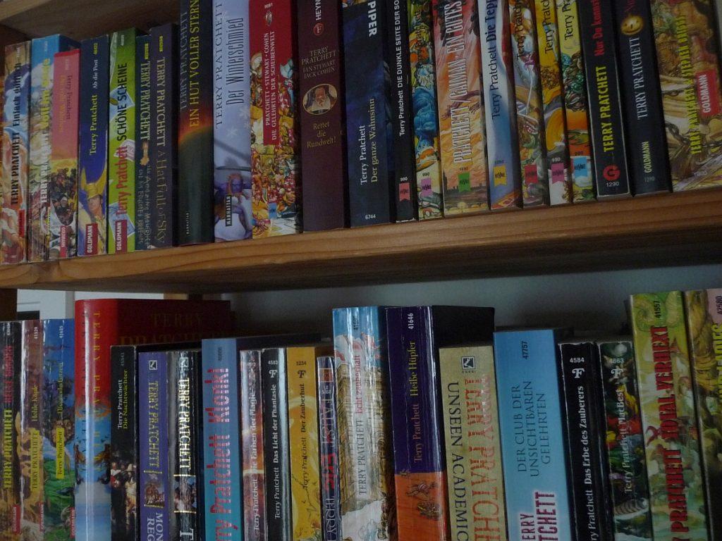 Zwei Regalbretter voll mit Terry-Pratchett-Büchern