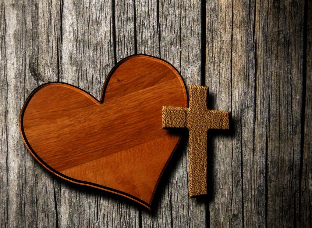 Ein Herz aus Holz und ein Kreuz, mit Stoff überzogen, liegen nebeneinander
