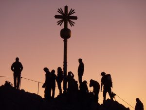 Bergsteiger am Gipfelkreuz