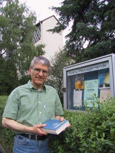 Pfarrer Helmut Schütz steht im Jahr 2004 mit der Bibel in der Hand vor dem Schaukasten der Paulusgemeinde