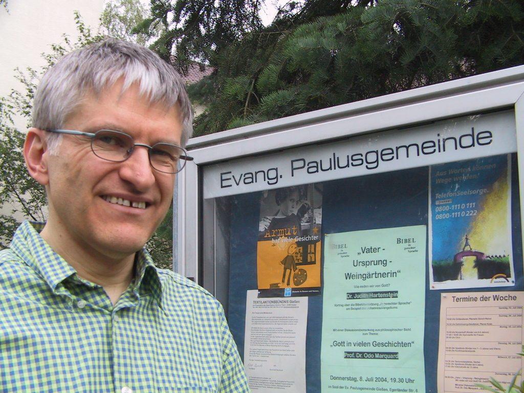 Pfarrer Helmut Schütz im Jahr 2004 vor dem Schaukasten der Evangelischen Paulusgemeinde Gießen
