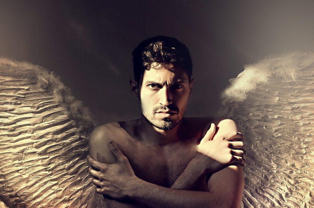 Ein Mann mit nacktem Oberkörper, der mit seinen Händen die eigenen Oberarme umfasst und mit Flügeln dargestellt ist