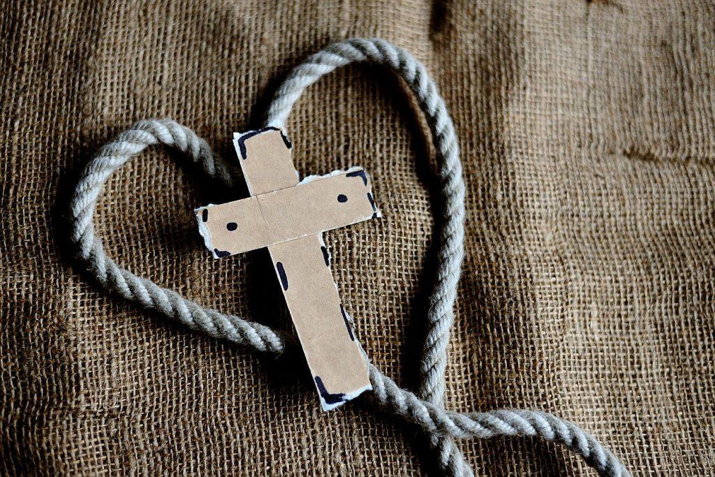 Ein Kreuz in einer zu einem Herzen geformten Kordel