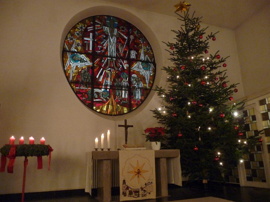 Weihnachtlich geschmückte Pauluskirche in der Gießener Nordstadt mit Weihnachtsbaum und Adventskranz vor dem von außen erleuchteten Altarfenster