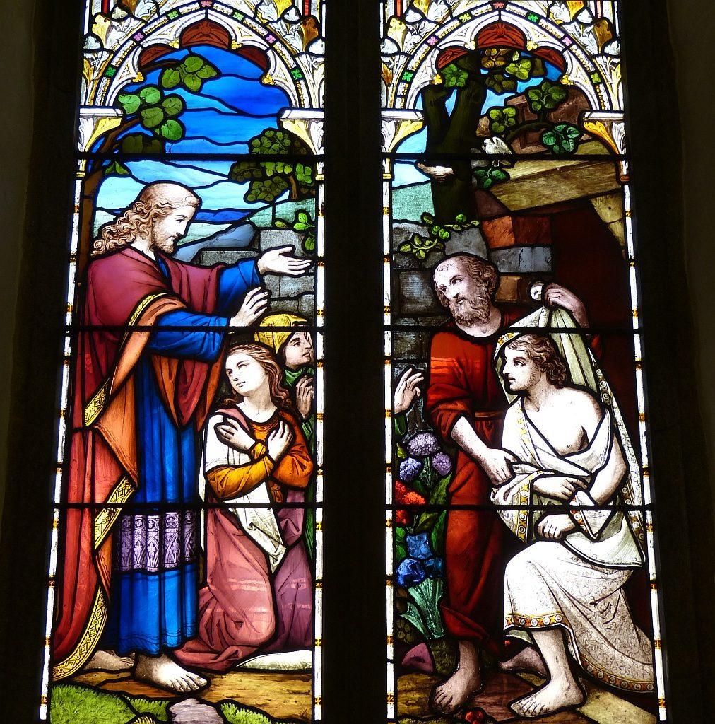 Kirchenfenster der Auferweckung des Lazarus durch Jesus, dabei knien Maria und Marta, ein Mann löst dem Lazarus die Binden