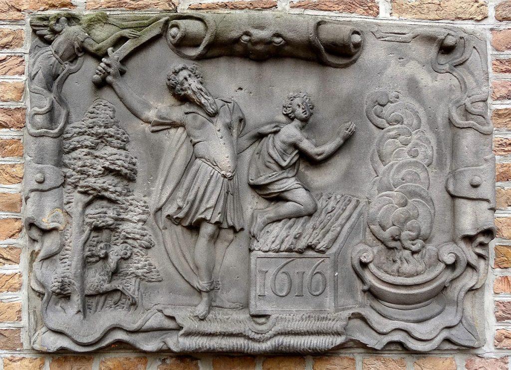 Relief an einer Hauswand: Abraham schwingt das Messer über dem auf einem Altar knienden Isaak - ein kaum sichtbarer Engel fasst das Messer an