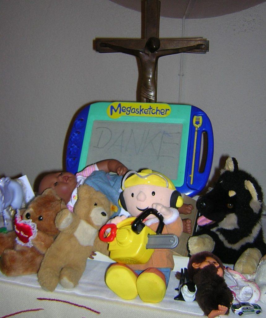 Megasketcher, Bob der Baumeister, Teddies und anderes Spielzeug beim Spielzeug-Erntedankfest vor dem Altarkreuz der Pauluskirche