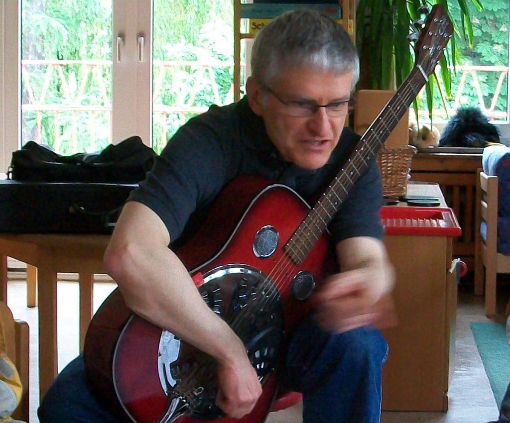 Pfarrer Schütz mit seiner Metallresonator-Gitarre