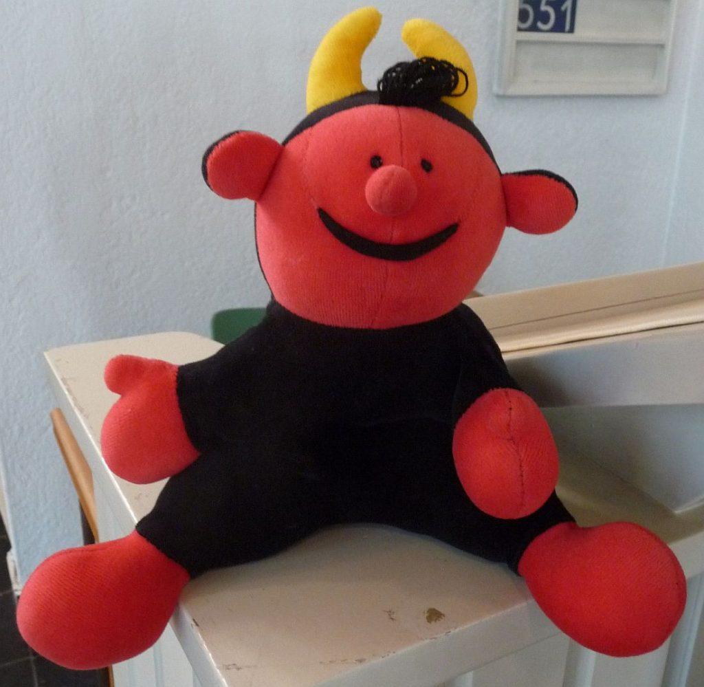 Handpuppe Lutz, der wie ein roter Teufel aussieht, auf der Kanzelbrüstung sitzend