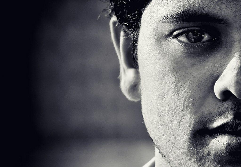 Ein halb zu sehendes ernstes Gesicht eines Mannes, Schwarzweiß-Foto, ein großes Auge blickt den Betrachter an