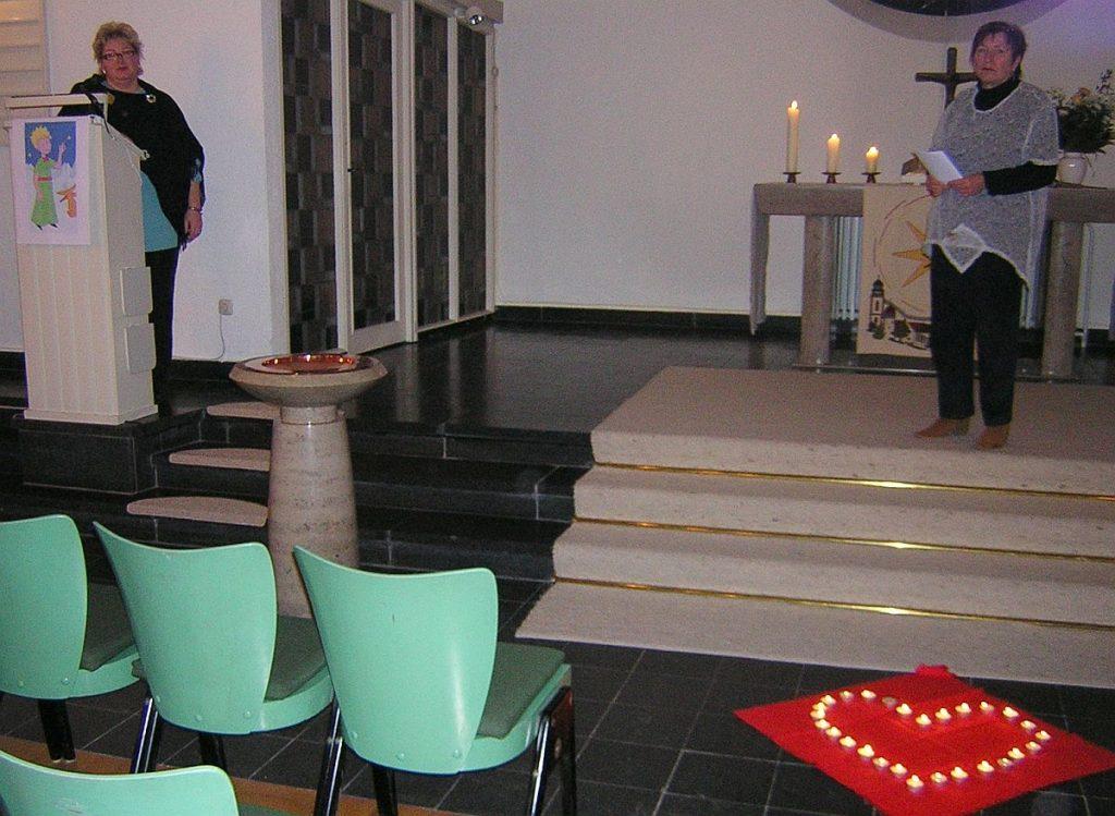 Frau Burk und Frau Garth haben vor den Altarstufen ein Herz aus Teelichtern aufgestellt