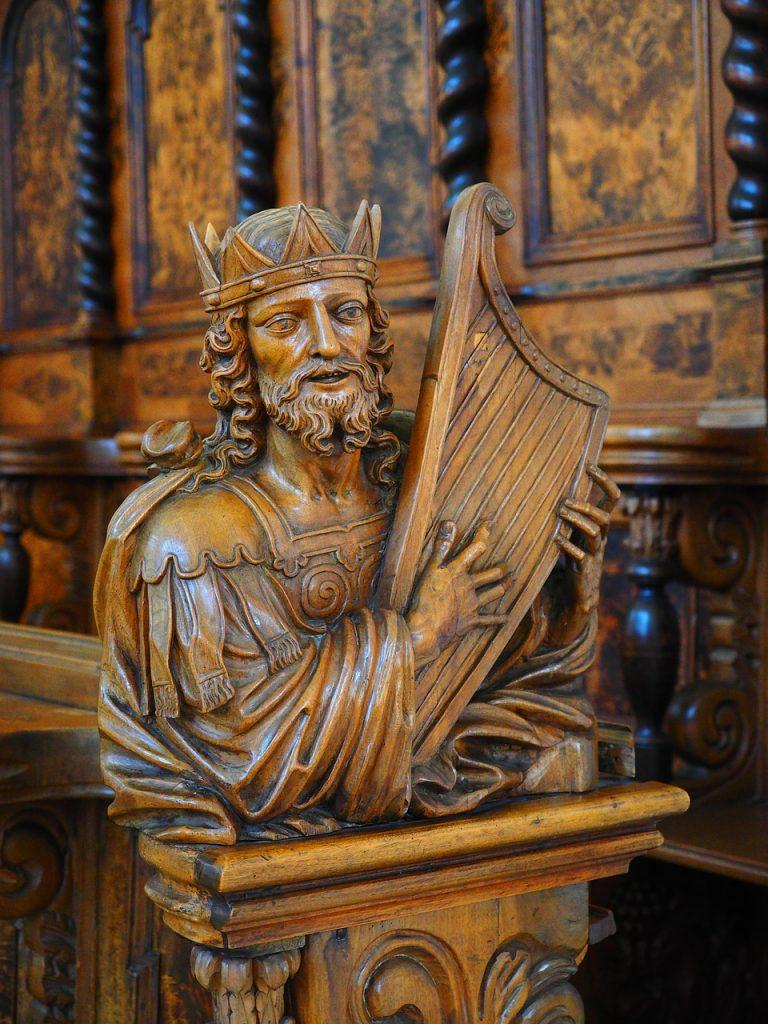 Skulptur aus Holz: König David spielt auf seiner Harfe