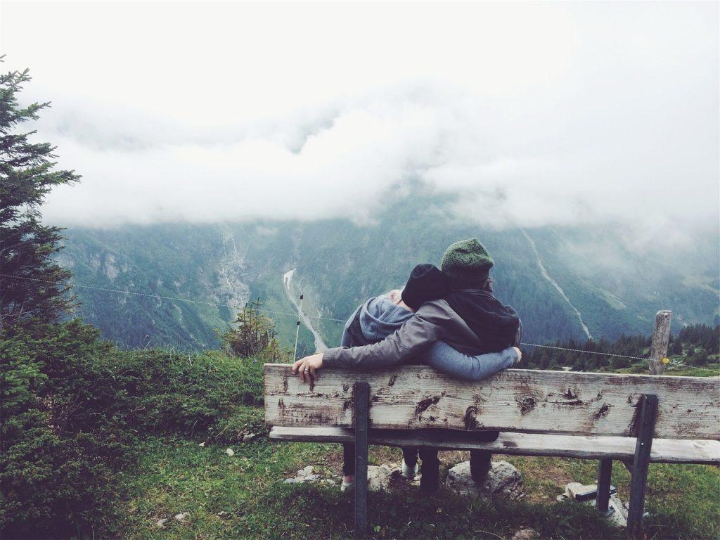 Durchsichtige Hände Gottes - wie kann man sie spüren? Paar auf einer Bank in enger Umarmung von hinten mit Blick auf Berge oder Hügel, die hinter Wolken versteckt sind