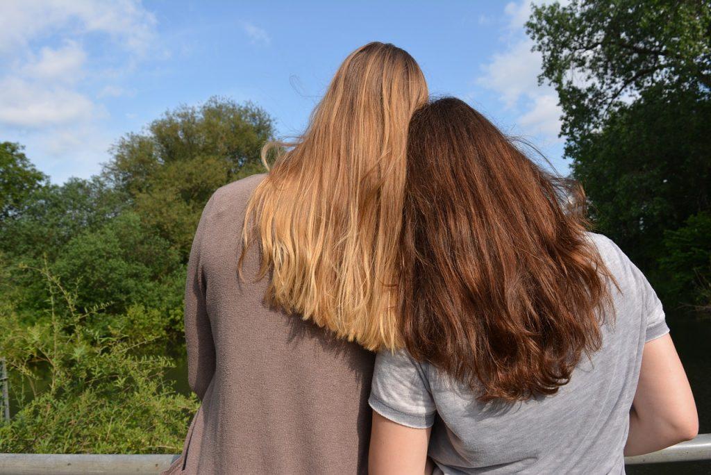 Zwei beste Freundinnen von hinten gesehen, wie sie sich aneinander lehnen