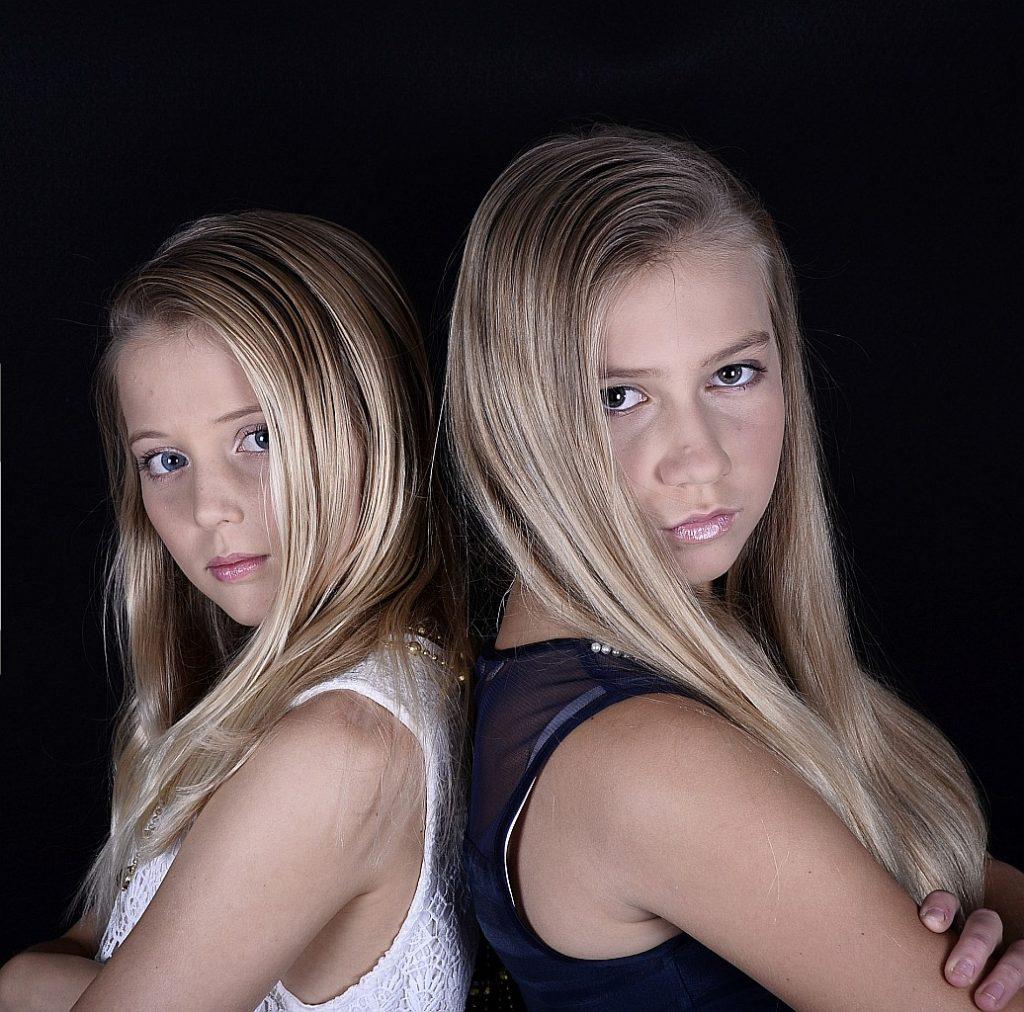 Zwei Mädchen, mit dem Rücken aneinandergelehnt, schauen mit ernstem Gesicht in die Kamera