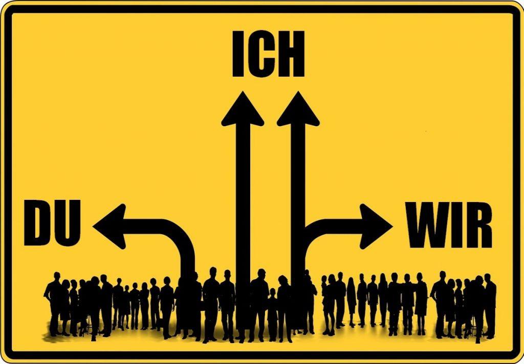 Gelbes Hinweisschild mit Silhouetten von vielen Menschen unten und Pfeilen zum DU, zum ICH und zum WIR