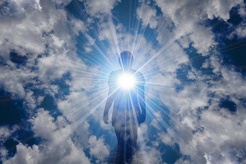 Kann Sterben ein Gewinn sein? Das Bild zeigt die Silhouette einer Frau vor einem Wolkenhimmel, aus ihrer Mitte strahlt ein helles Licht