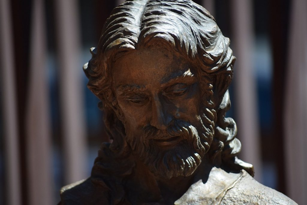 Statue von Jesus, dessen Gesicht im Schatten liegt, angestrahlt ist nur sein Haar und seine linke Schulter von rechts oben: Jesus, wer bist du?