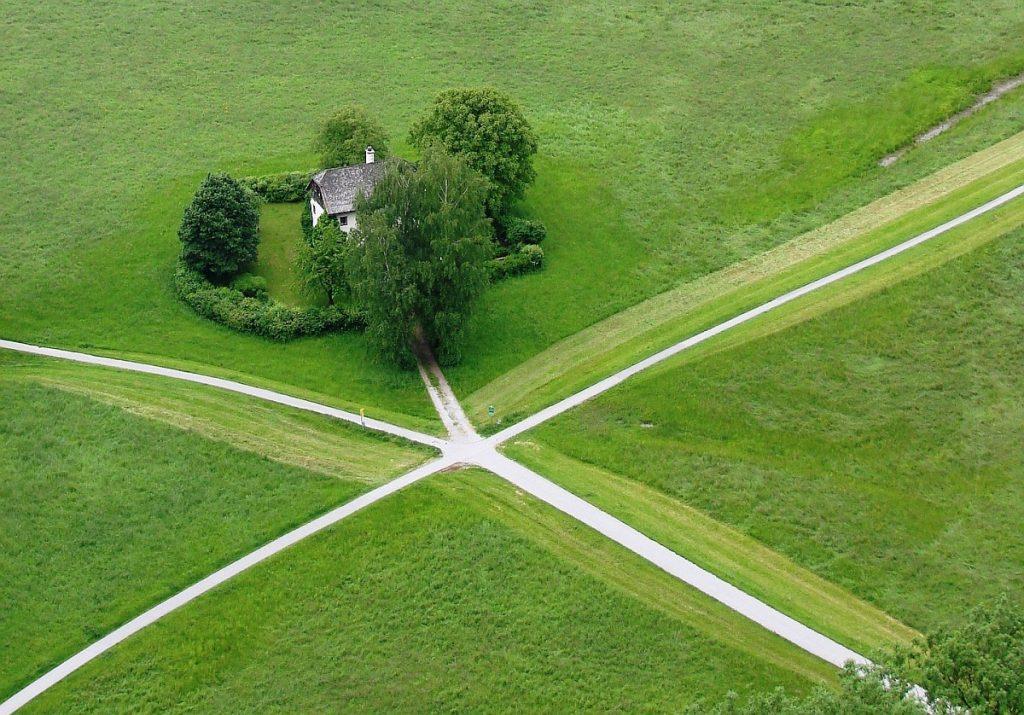 Weggabelung: Fünf Wege gabeln sich, einer führt zu einem kleinen umfriedeten Häuschen im Grünen