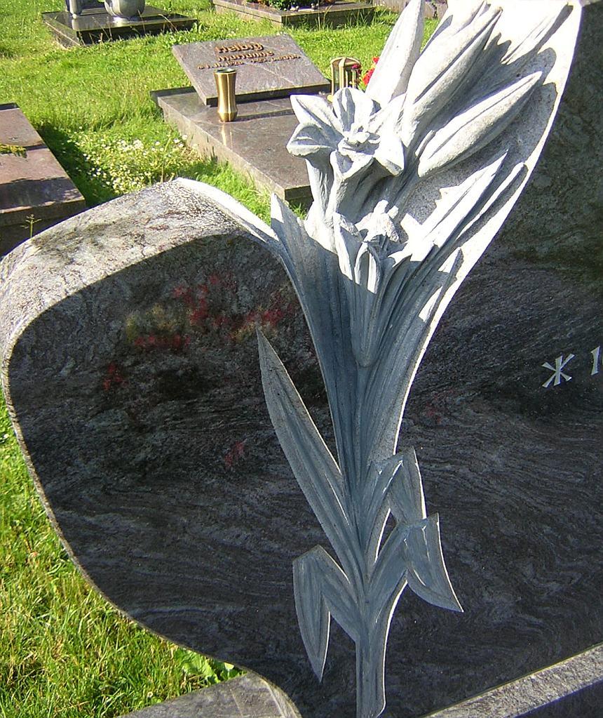 Lilie als Skulptur in einen Grabstein eingepasst