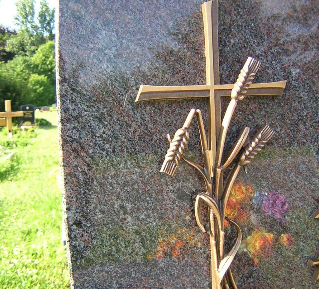 Kreuz mit einer geknickten und zwei unversehrten Ähren auf einem Grabstein