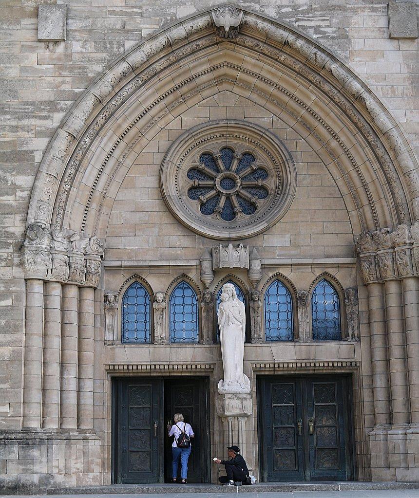 Ein Bettler sitzt an einer Kirchentür, an ihm vorbei geht eine Frau in die Kirche