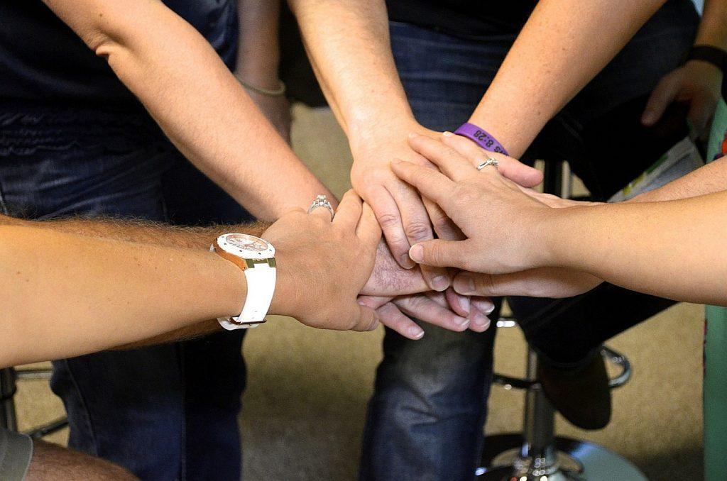 Hände eines Teams halten einander Fest: eine Gemeinschaft der Heiligen?
