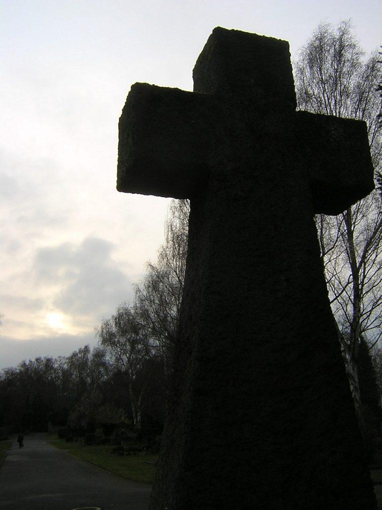 Das Steinkreuz auf dem Neuen Friedhof im Gegenlicht des Ostermorgens