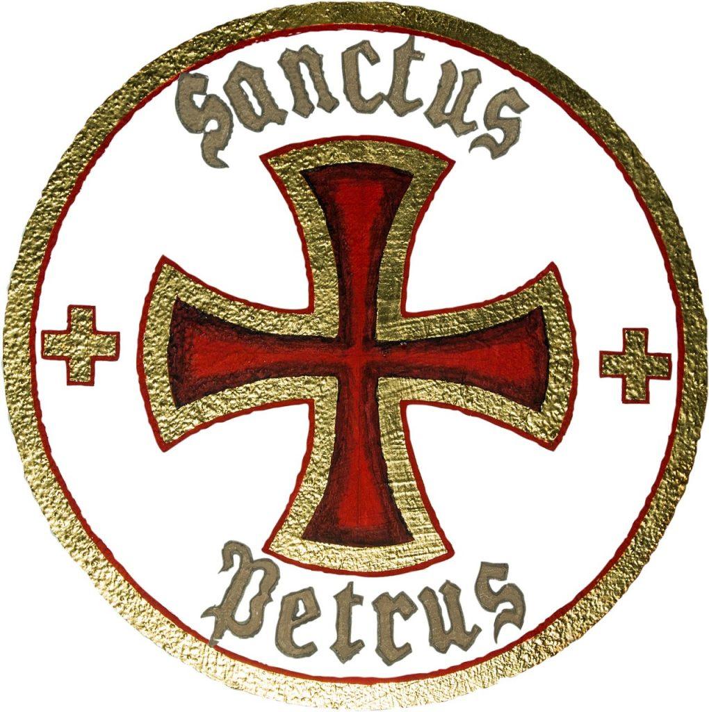 """Ein rotgoldenes Kreuz in rotgoldenem Kreis mit Schriftzug """"Sanctus Petrus"""""""