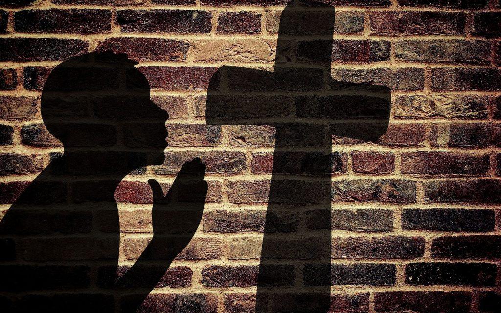 Der Schatten eines betenden jungen Mannes vor dem Kreuz fällt auf eine Ziegelwand