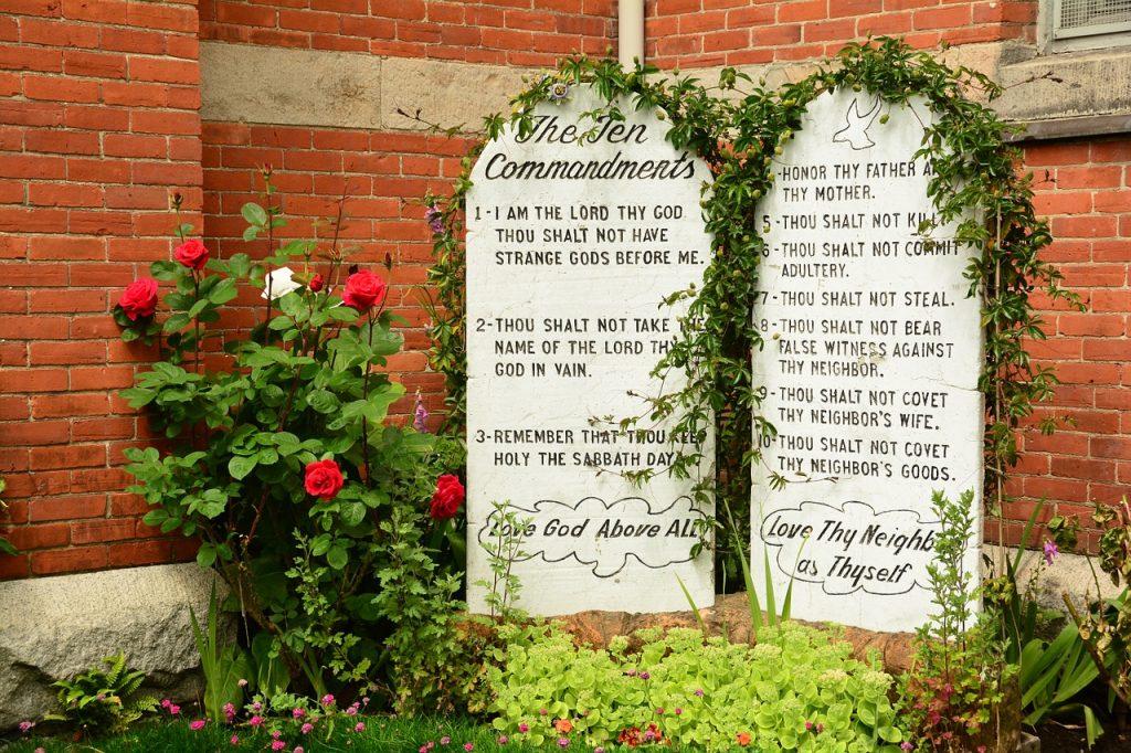 Die Zehn Gebote auf Steintafeln (in englischer Sprache) neben einem Rosenbusch