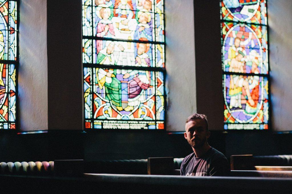 Ein Mann sitzt in einer Kirche vor sonnendurchfluteten Kirchenfenstern