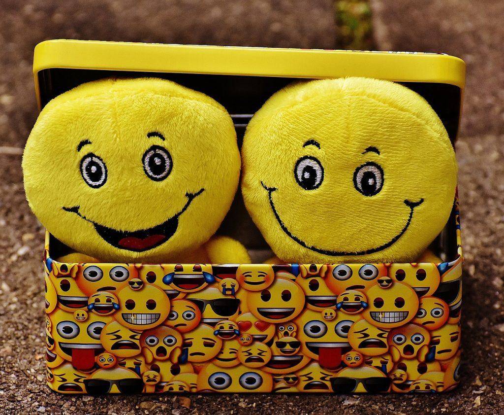 Zwei Stoff-Smilies, ein lachendes und ein lächelndes, in einer mit vielen Smilies bedruckten Kiste