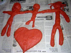 Aus Ton gestaltet: ein Herz mit Schriftzug Peace sowie Vater, Mutter, Kind, die sich an den Händen halten