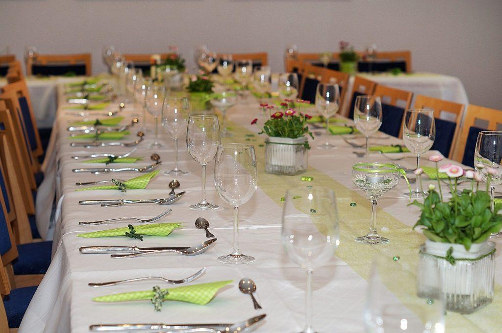 Ein gedeckter Tisch mit Besteck, Gläsern, Servietten und Dekorationen