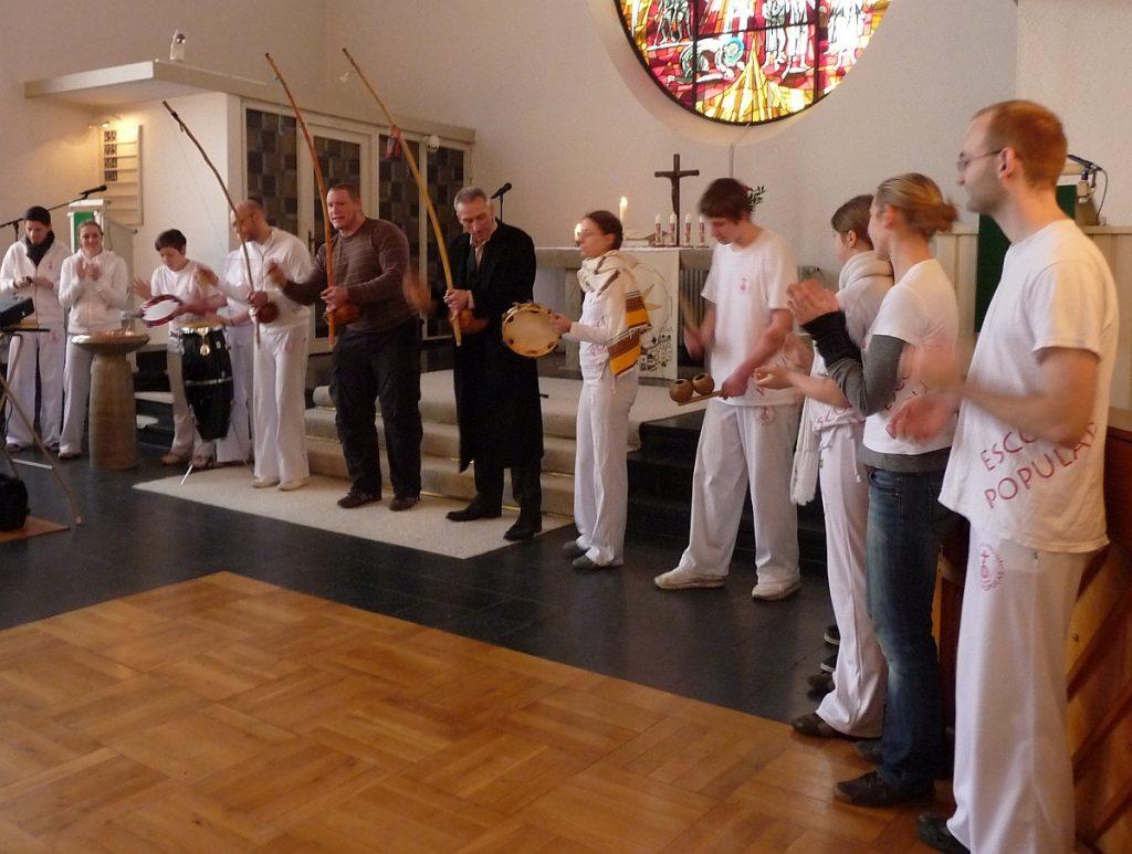 Die Capoeira-Gruppe ist in die Pauluskirche eingezogen und stellt sich vor dem Altarraum auf