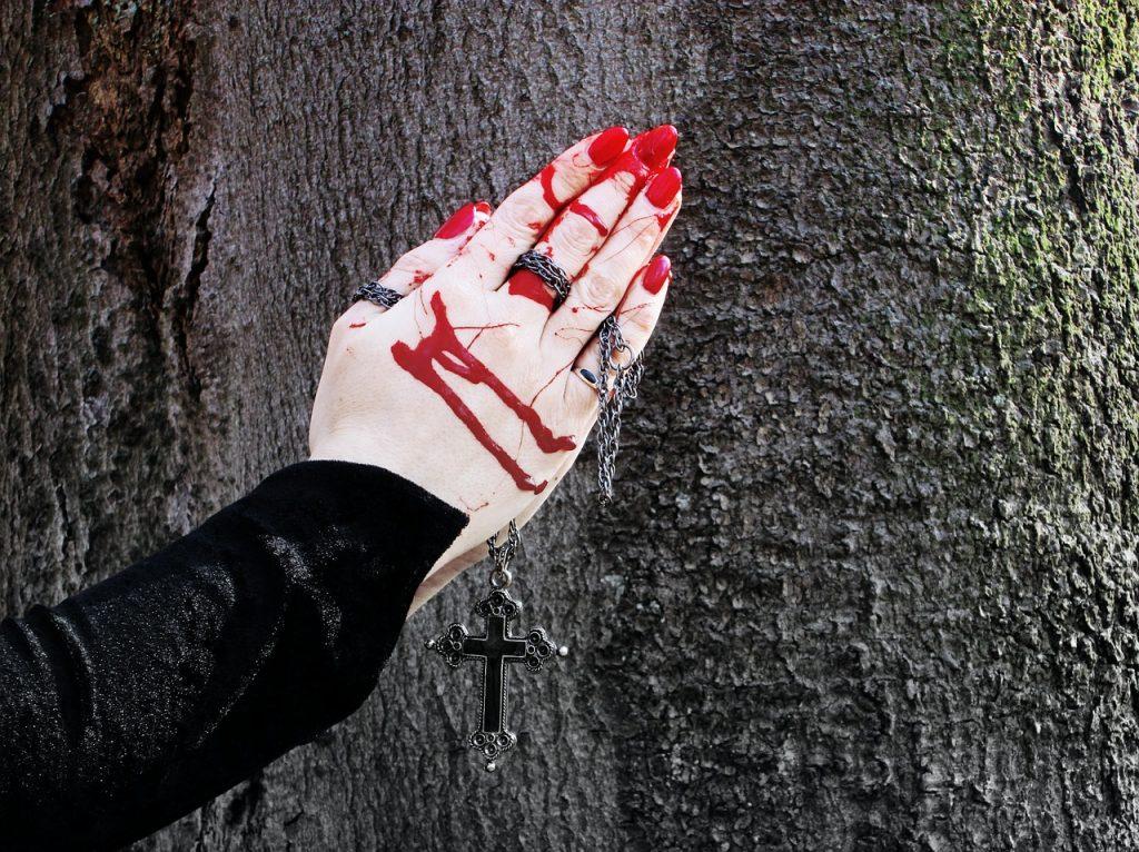 Die blutigen und zum Gebet zusammengelegten Hände einer Frau halten ein Kreuz vor einem Baumstamm