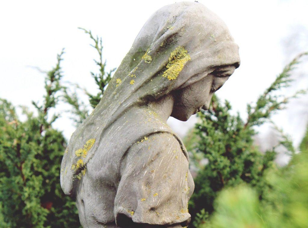 Statue eines Mädchens mit gesenktem Kopf