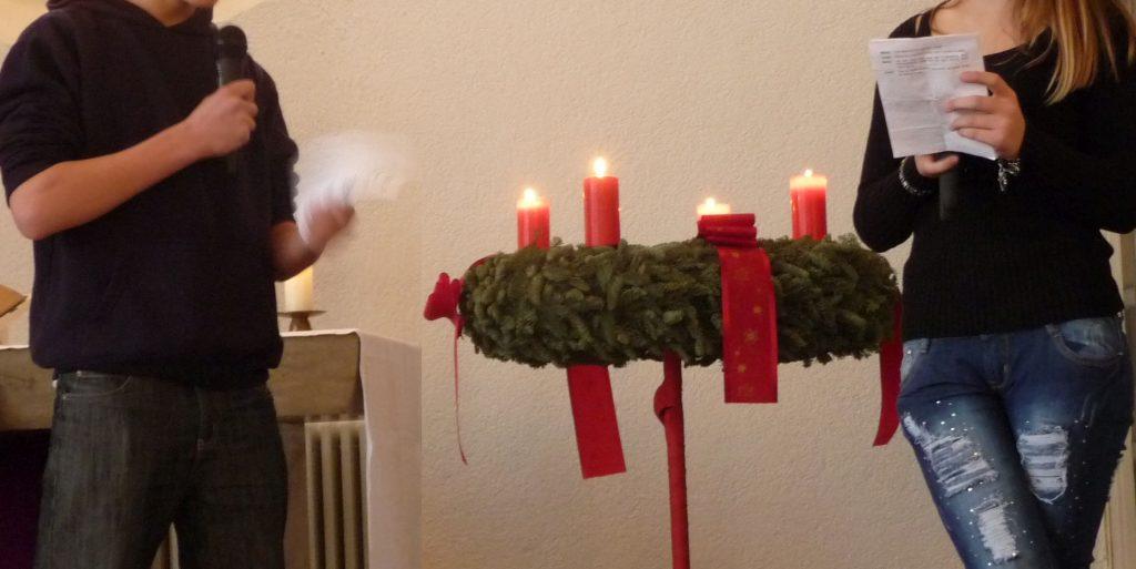 Konfis inszenieren das Gespräch zwischen Josef und Maria vor dem Adventskranz, an dem vier Kerzen brennen