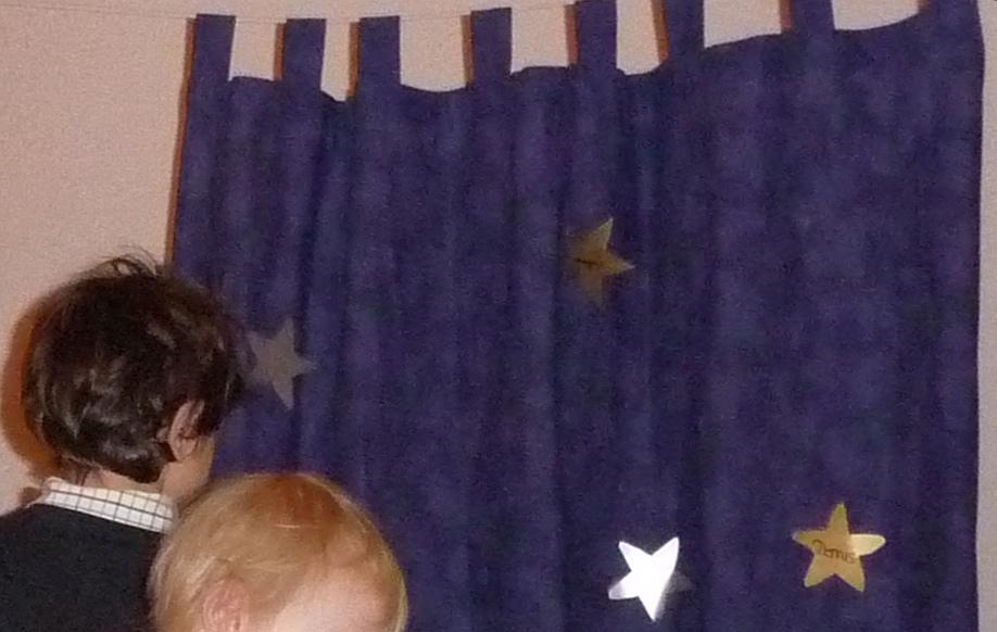 Die Wünsche der Kinder werden auf Sternen an Tüchern befestigt, die vorn im Altarraum hängen
