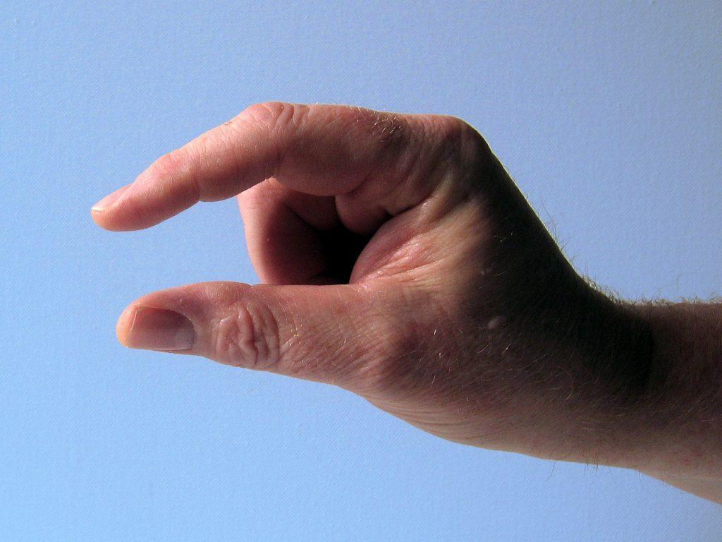 Jemand deutet mit seiner Hand einen kurzen Abstand zwischen Daumen und Zeigefinger an
